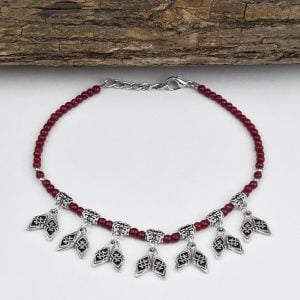 Oxidised Silver Red Beads Charms Bracelet On Wooden Log