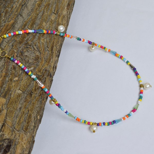 Hand Beaded Dainty and Colorful Pearl Necklace On Wooden Log